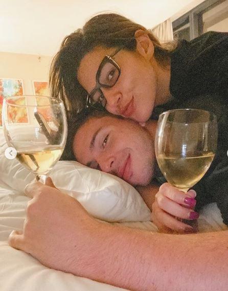 Na foto Vivian Amorim e seu namorado Leo deitados em uma cama cada um com uma taça de vinho na mão