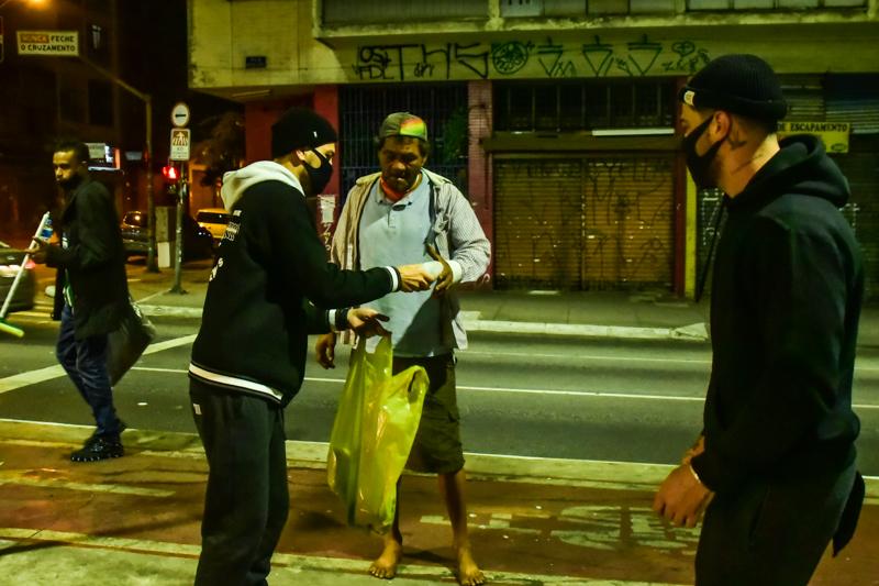 Felipe Titto entrega cobertor a morador de rua - Foto Leo Franco/ Agnews
