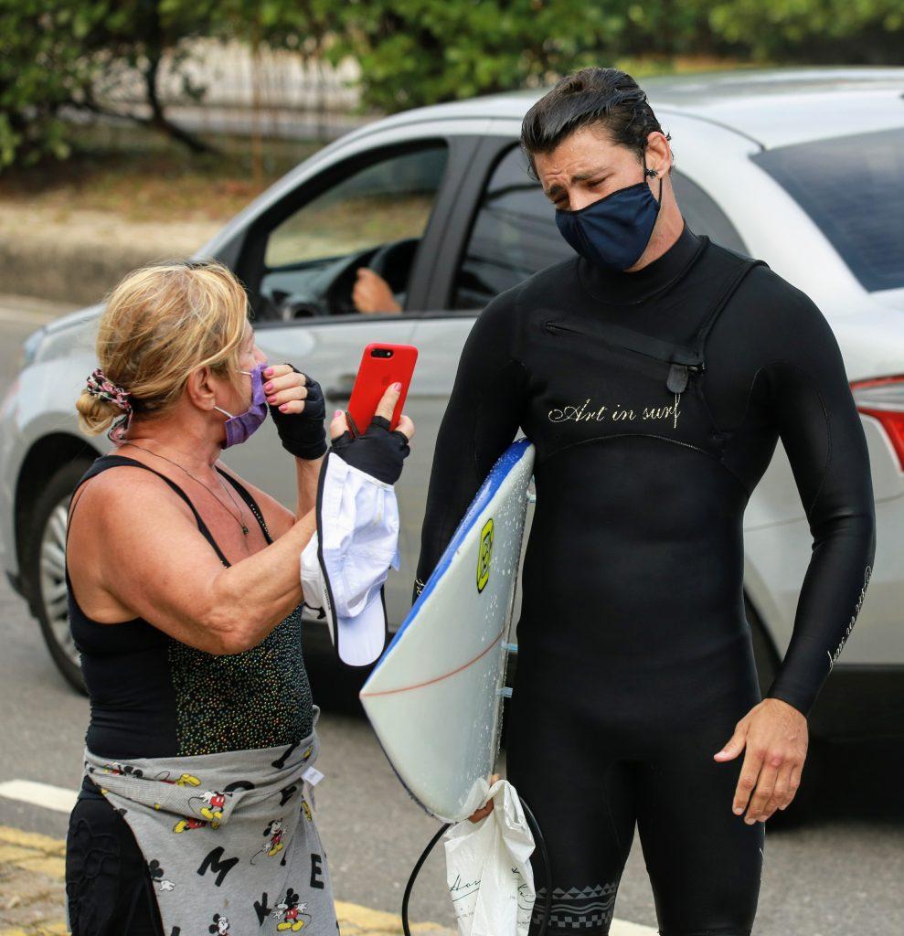 Cauã com roupa de surfista sendo tietado na orla da Barra da Tijuca