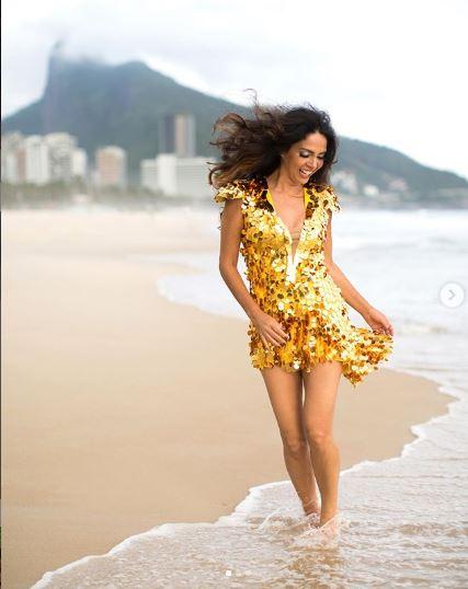 Claudia Ohana em praia carioca com um vestido brilhoso dourado e cabelos ao vento