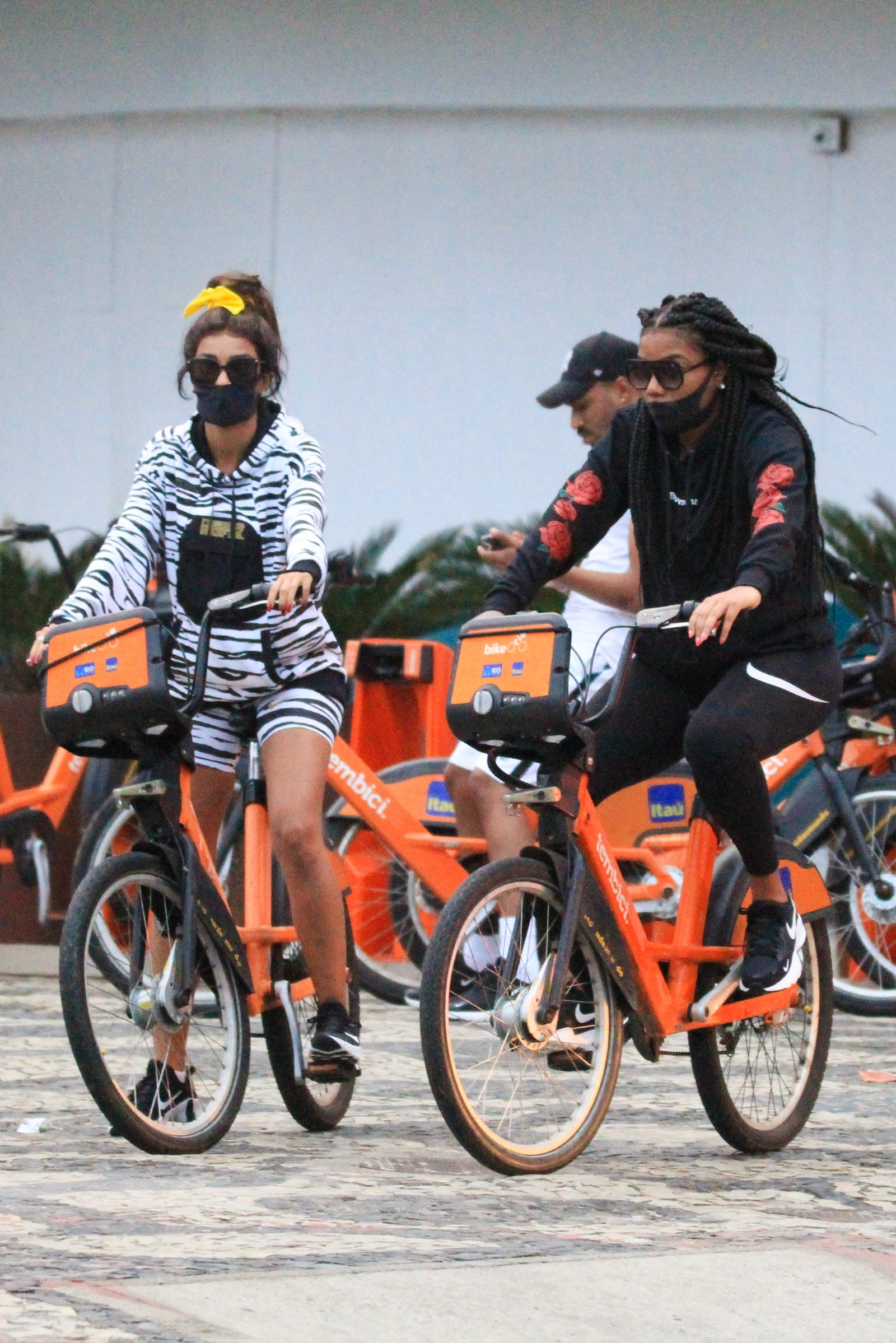 Ludmilla e Brunna passeiam de bicicleta e trocam beijos de máscara