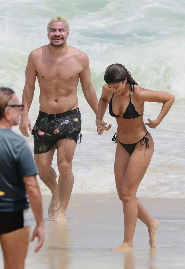 Thiago Martins e sua namorada saem do mar. Ele com calção, ela com biquini