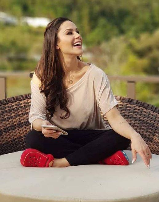 Nadja Haddad sentada em posição indiozinho com sorriso aberto