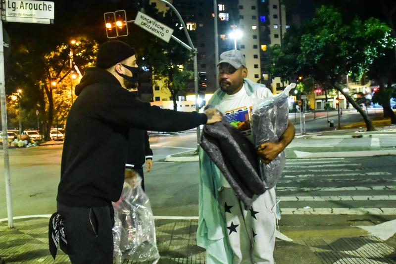 Felipe Titto entrega cobertor a morador de rua – Foto Leo Franco/ Agnews