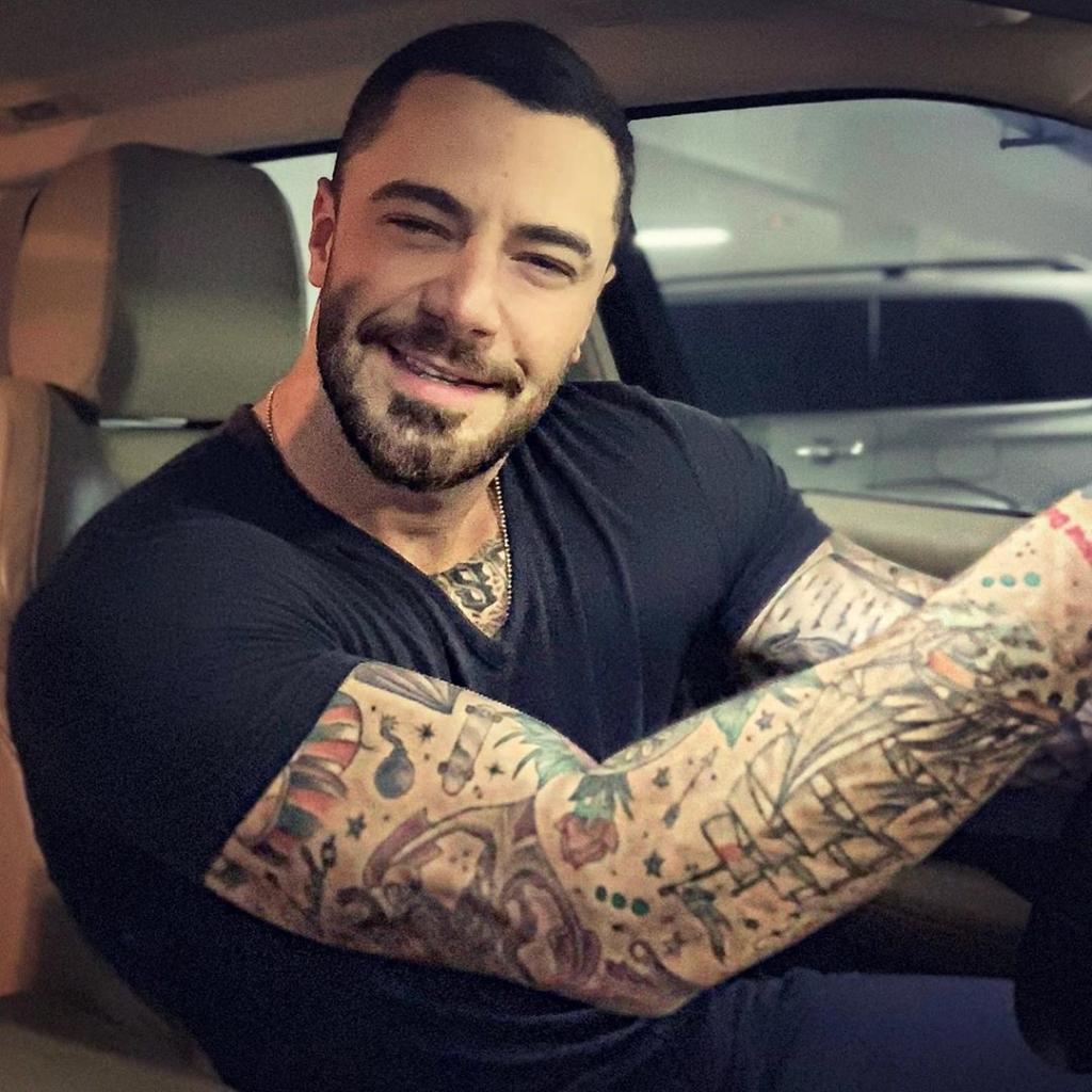 Felipe Titto em seu carro com os braços tatuados