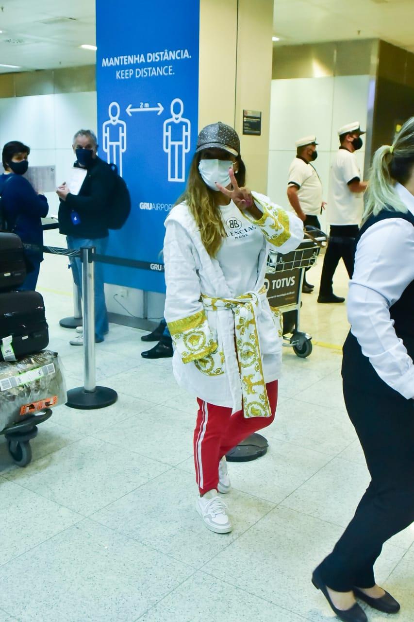Anitta chega ao Brasil de roupão após férias na Europa
