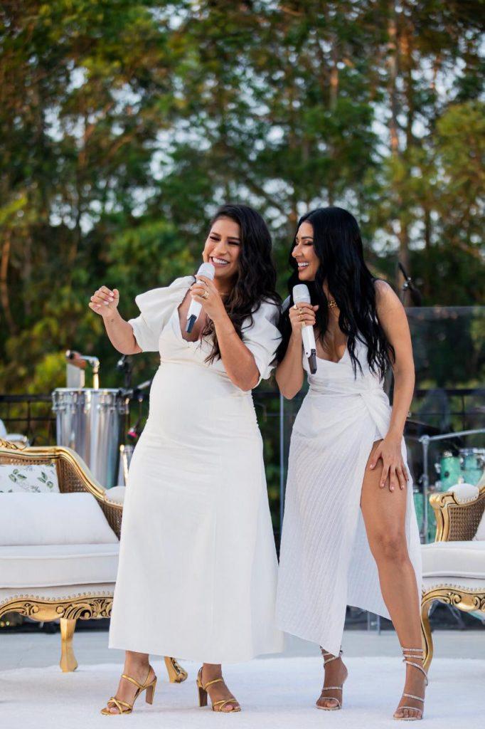 Coleguinhas de vestido branco e microfone nas mãos.