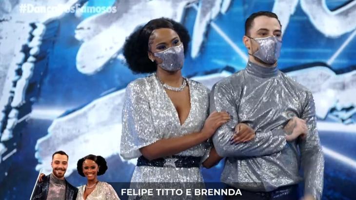 foto da apresentação do casal no dança dos famosos. Os dois de cinza e máscara