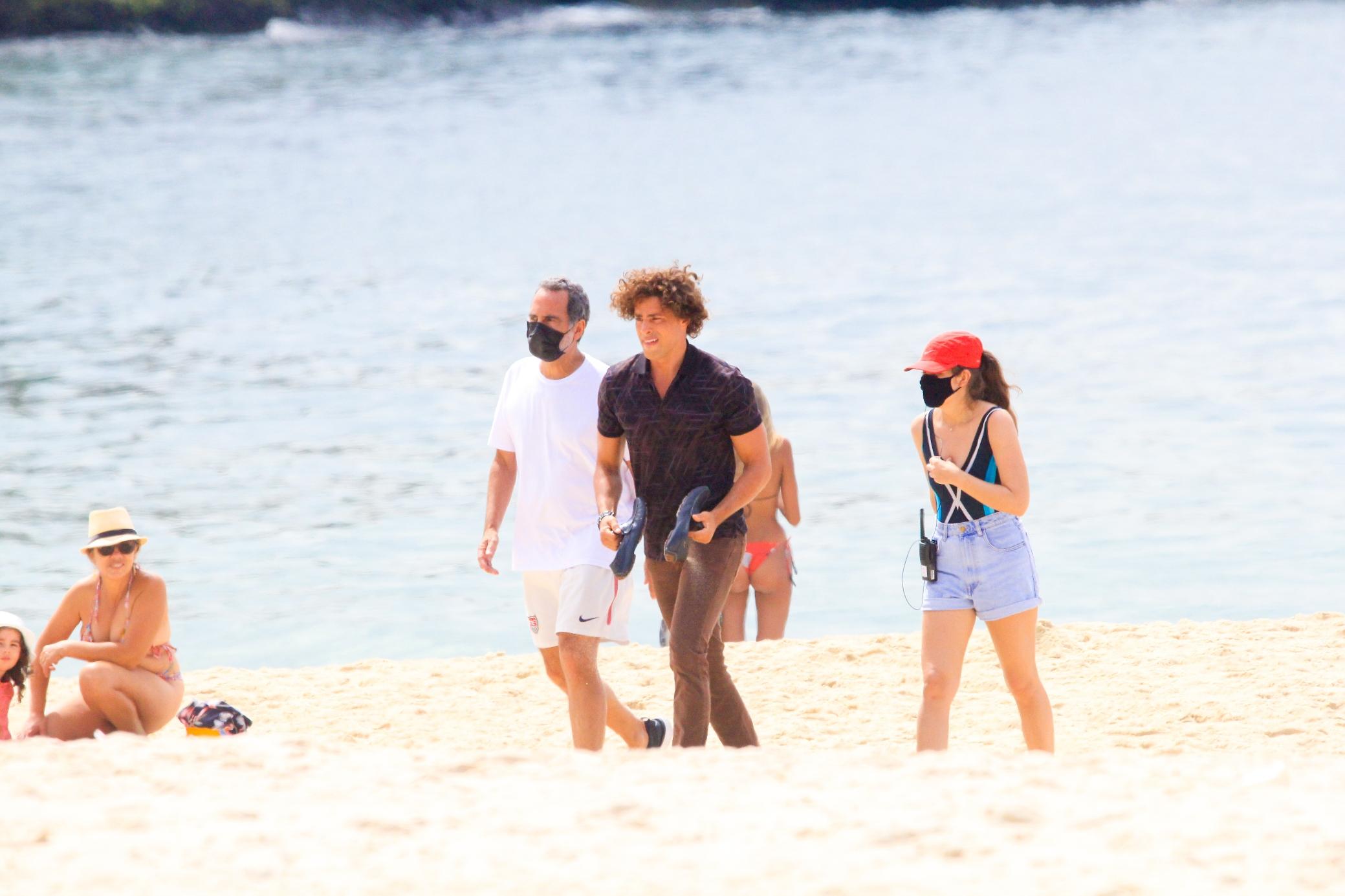 Cauã Reymond surge com novo visual em gravação na praia