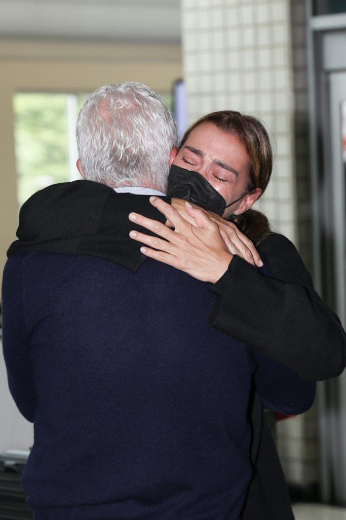 Mônica Martelli chora nos braços de seu pai após morte de Paulo Gustavo