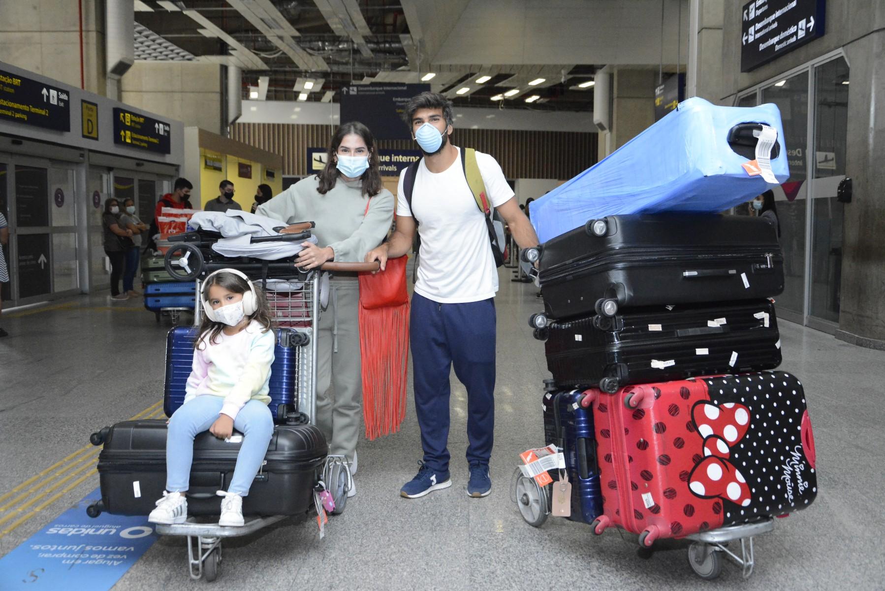 Cheia de malas, Deborah Secco retorna ao Brasil com a família