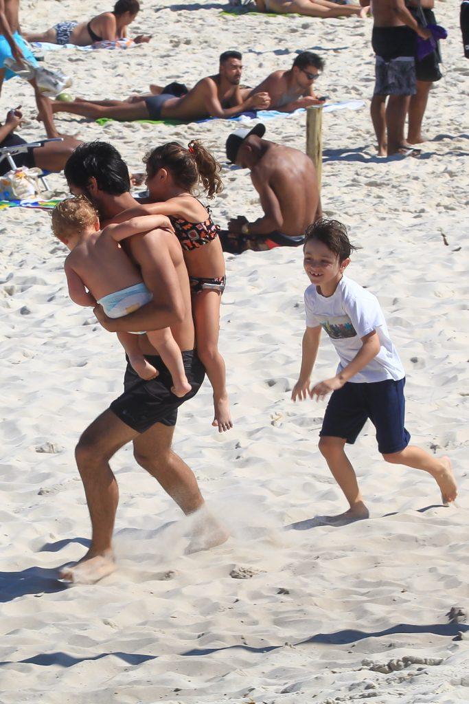 Felipe Simas se diverte com os três filhos em praia